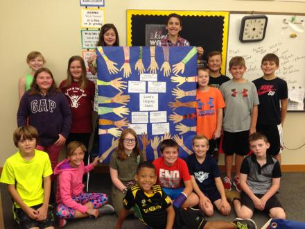 Students surround a poster of their helping hands - Community Service