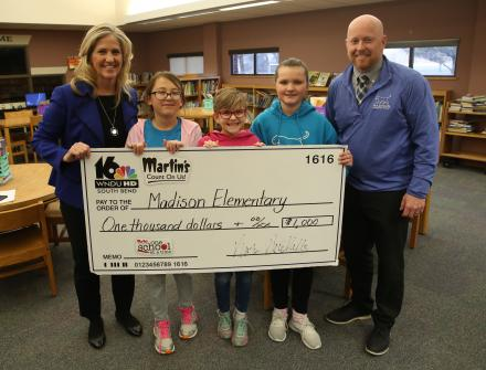 WNDU's Tricia Sloma (left) presenting their check with Madison Elementary School Principal Kevin McMillen (right) and Madison Students