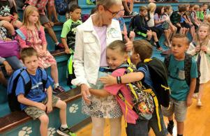 Excited students hug Kindergarten Aide Joyce Zalas